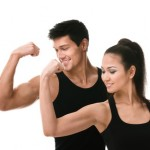 Two sportive people in black sportswear showing their biceps, isolated on white